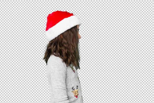 Little girl celebrating christmas day gazing left, sideways pose.