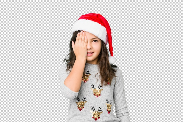 Little girl celebrating christmas day having fun covering half of face with palm.