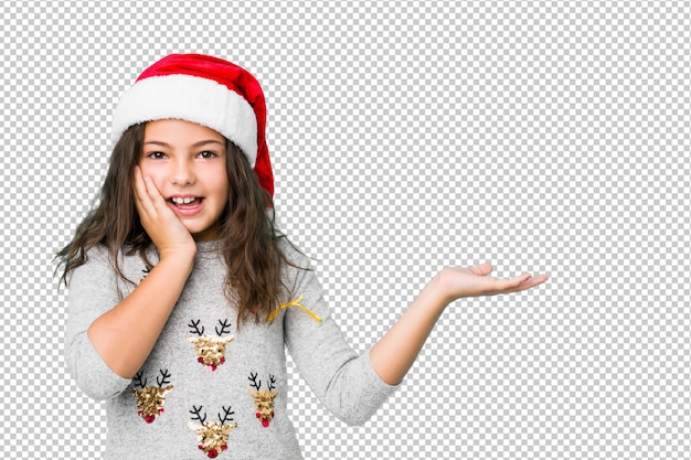 Little girl celebrating christmas day holds copy space on a palm, keep hand over cheek. amazed and delighted.