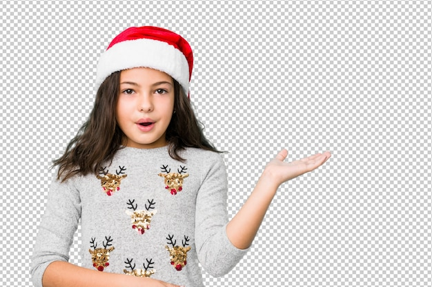 Little girl celebrating christmas day impressed holding copy space on palm.