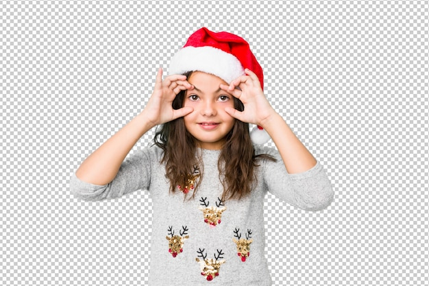 Little girl celebrating christmas day keeping eyes opened to find a success opportunity.