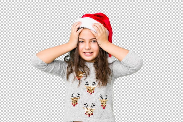 Little girl celebrating christmas day laughs joyfully keeping hands on head. happiness concept.