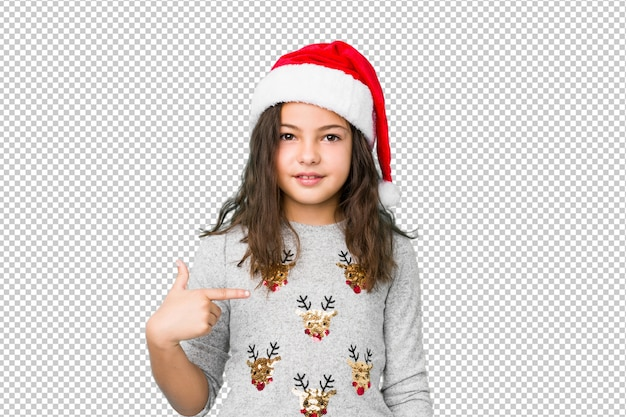 Little girl celebrating christmas day person pointing by hand to a shirt copy space, proud and confident
