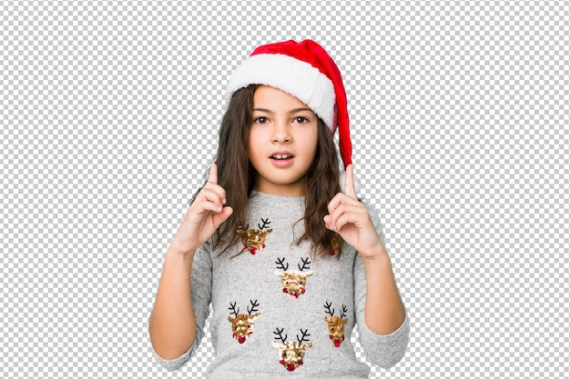 Little girl celebrating christmas day pointing upside with opened mouth.