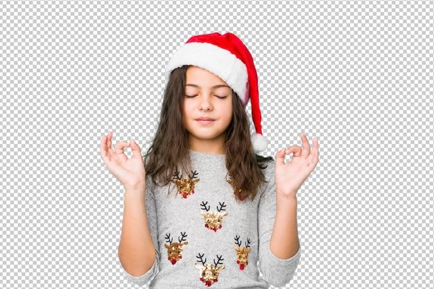 クリスマスの日を祝う少女は懸命に仕事をした後リラックスし、ヨガを行っています。