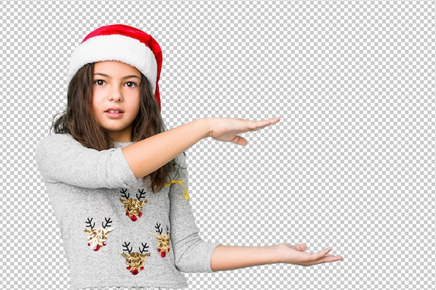 Little girl celebrating christmas day shocked and amazed holding a copy space between hands.