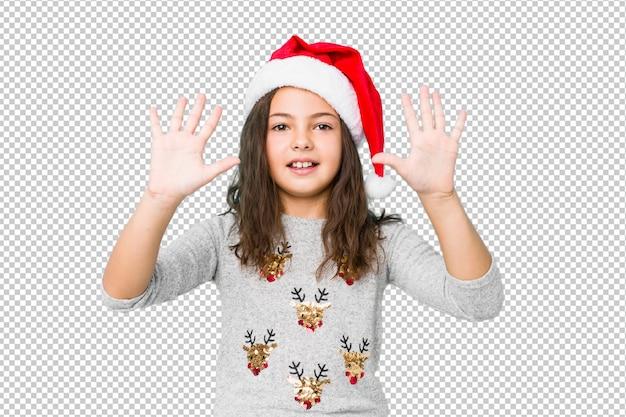 손으로 숫자 10을 보여주는 크리스마스를 축 하하는 어린 소녀.