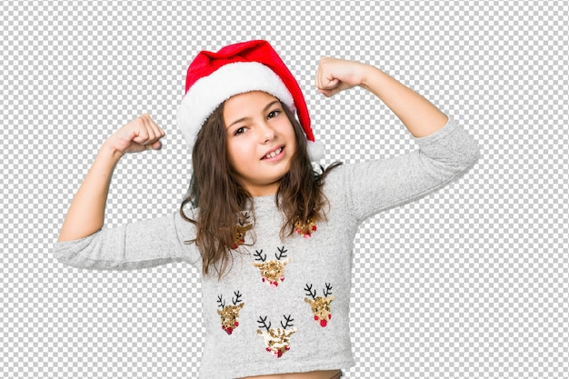 Little girl celebrating christmas day showing strength gesture with arms, symbol of feminine power