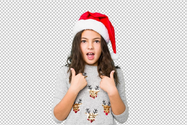 Little girl celebrating christmas day surprised pointing with finger, smiling broadly.