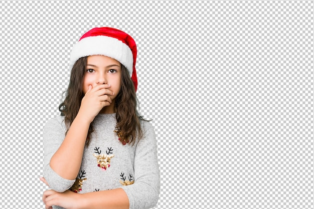 Little girl celebrating christmas day thoughtful looking to a copy space covering mouth with hand.
