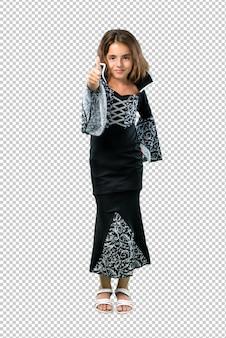 어린 소녀는 엄지 손가락 제스처를 포기하고 할로윈 휴일 뱀파이어처럼 옷을 입고