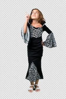 검지 손가락으로 좋은 아이디어를 가리키는 할로윈 휴가를위한 뱀파이어처럼 옷을 입은 어린 소녀