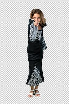 할로윈 휴가를위한 뱀파이어처럼 옷을 입은 어린 소녀가 손가락을 가리 킵니다.