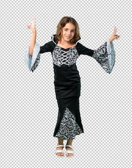 웃 고 승리 기호를 보여주는 할로윈 휴일 뱀파이어로 분 장 한 어린 소녀