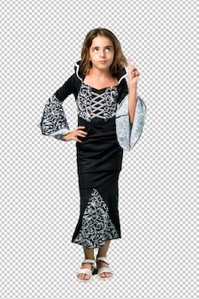 Little girl dressed as a vampire for halloween holidays standing and thinking an idea