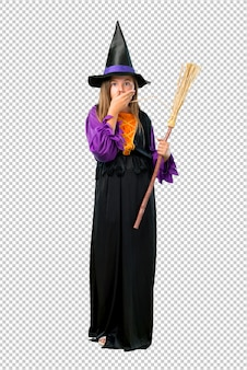 Little girl dressed as a witch for halloween holidays covering mouth with hands