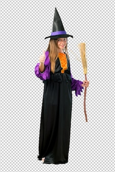 Little girl dressed as a witch for halloween holidays giving a thumbs up gesture and smiling