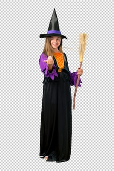 Little girl dressed as a witch for halloween holidays presenting and inviting to come