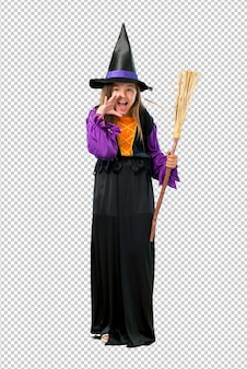 Little girl dressed as a witch for halloween holidays shouting with mouth wide open