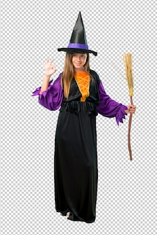 Little girl dressed as a witch for halloween holidays showing an ok sign with fingers