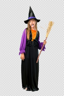 Little girl dressed as a witch for halloween holidays showing tongue at the camera having funny look