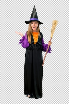 Little girl dressed as a witch for halloween holidays with surprise and shocked facial expression