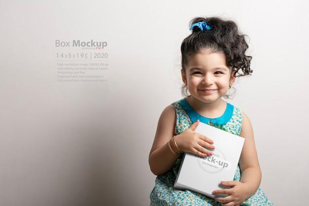 Маленькая девочка держит в руках небольшую кубическую подарочную коробку
