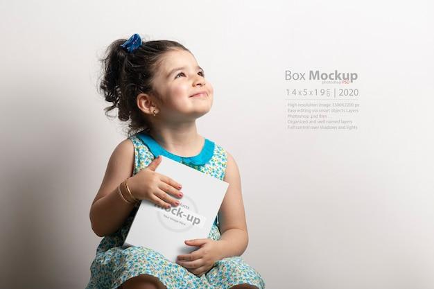 Маленькая девочка держит в руках небольшую подарочную коробку