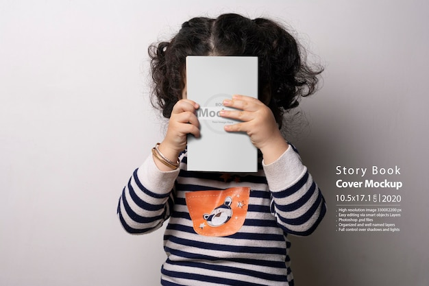 Little girl holding a children story book with cover mockup
