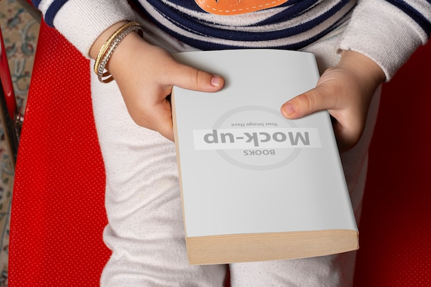 Little girl holding a novel book with blank cover in front of body