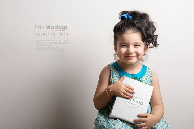 Little girl holding a small cubical gift box in hands