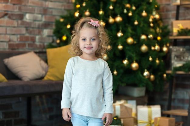 디자인을위한 모형 스웨터와 함께 크리스마스 트리 옆에있는 어린 소녀