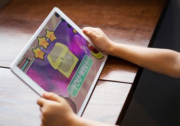 디지털 태블릿에 게임을하는 어린 소녀