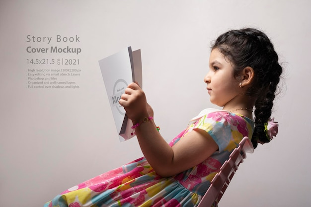 Little girl reading a book with blank cover in front of body