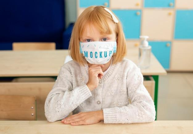 医療用マスクのモックアップを身に着けている少女