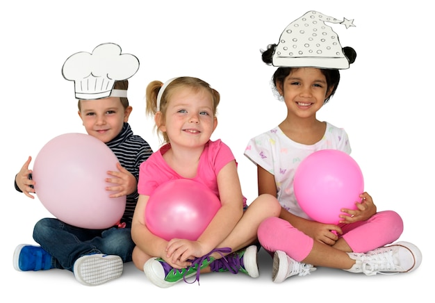 Little kids with papercrafted hats balloon