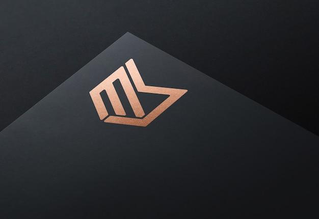 ブロンズ箔の黒い紙にロゴのモックアップ