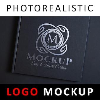 Макет логотипа - тиснение логотипа серебряной фольгой на черной обложке