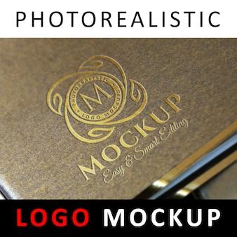 ロゴモックアップ - 黄金の織り目加工のカバーにロゴを押す