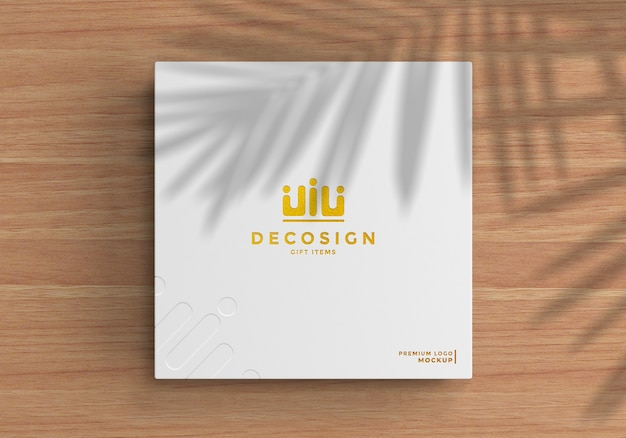 Logo mockup on a white box over a wooden table