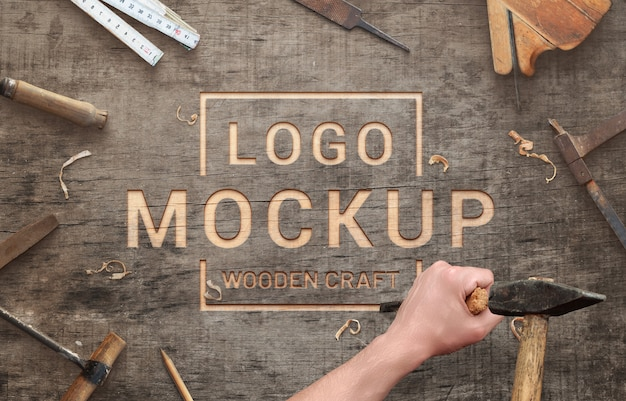 Logo mockup on wooden surface scene creator. carving with chisel and hammer concept.