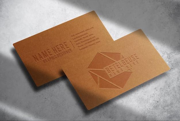 콘크리트 배경 모형이 있는 고급 부동 갈색 종이 양각 명함