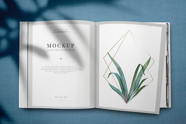 Mockup di rivista con foglie e cornice dorata