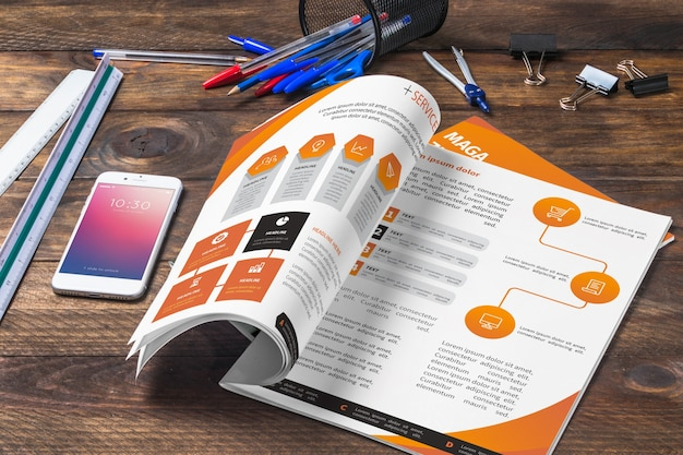 Magazine and smartphone mockup on wooden table with pens and rulers