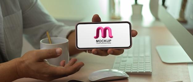 Мужчина-предприниматель показывает макет смартфона с горизонтальным экраном на офисном столе