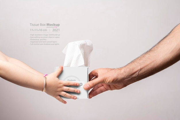 Male hand giving a cubical tissue box to little girl isolated