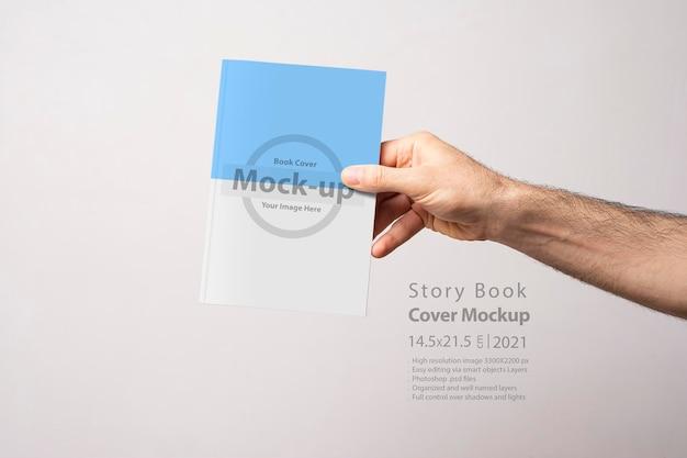 Мужская рука держит макет закрытой книги