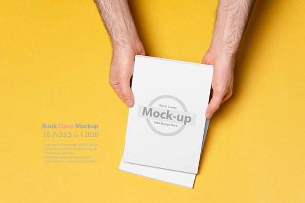 Male hand holding a closed book catalog isolated