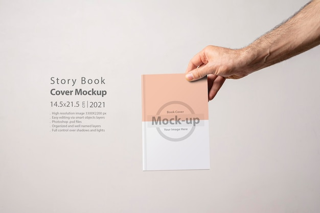 Male hand holding a closed bookcatalog with blank cover editable  mockup series with smart object layers