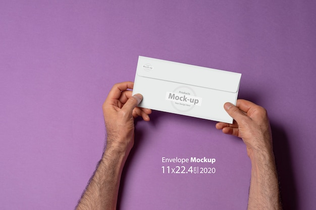 Male hand holding a letterhead paper envelope mock-up